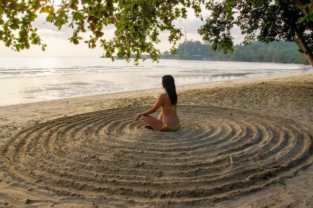 Het meisje leunt achterover op het zandstrand in het midden van een geïmproviseerde cirkel en mediteert