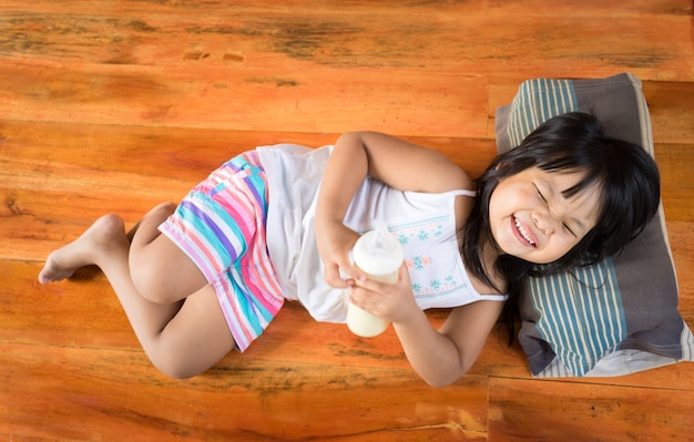 Het meisje ligt ontspannen terwijl het houden van een fles melk en het glimlachen