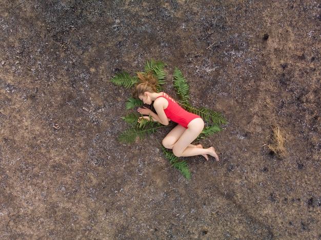 Het meisje ligt op de verschroeide aarde