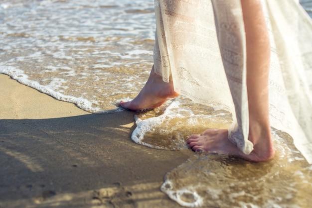 Het meisje loopt blootvoets op het zand in een witte kleding