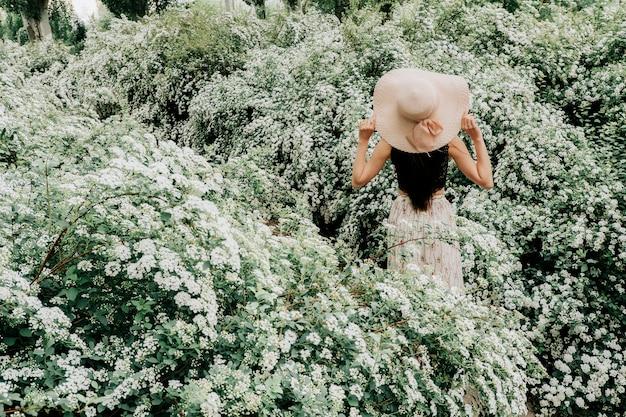 Het meisje loopt in een bloeiende tuin.
