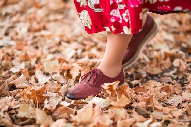 Het meisje loopt in het park. foto van vrouwelijke benen in kastanjebruine schoenen