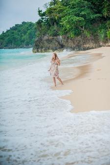 Het meisje loopt langs de waterkant op de boracay