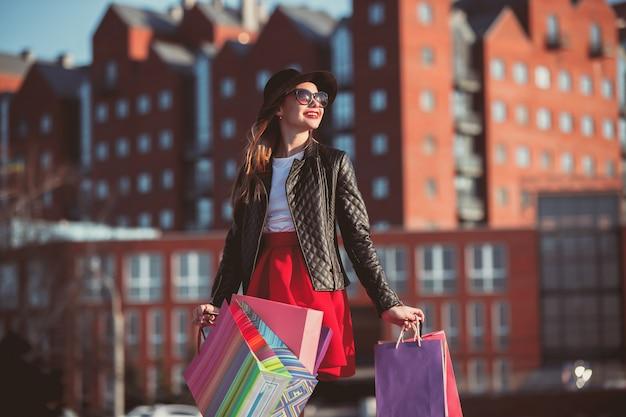 Het meisje loopt met boodschappentassen op de straten van de stad op zonnige dag