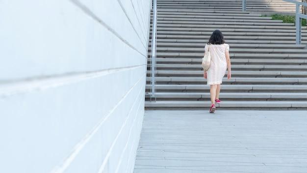 Het meisje loopt omhoog de externe concrete trede met de achtergrond van de landschapsstad.