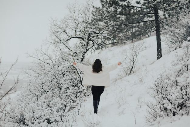 Het meisje loopt op een besneeuwde berg. idyllisch winterlandschap met besneeuwde bomen.
