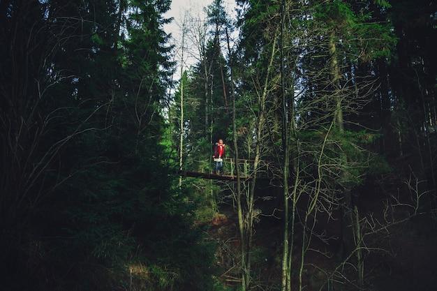 Het meisje loopt op een hangbrug over een bergrivier. donker, mystiek bos.