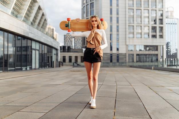Het meisje loopt op een longboard door de stad.