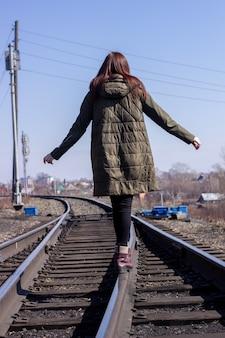 Het meisje loopt vooraan op de spoorlijn