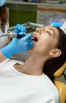 Het meisje lost gebitsproblemen op bij de tandarts
