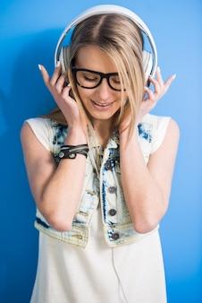 Het meisje luistert een muziek met hoofdtelefoon