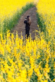 Het meisje maakt een foto in het gele bloemenveld.