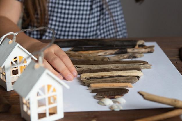 Het meisje maakt een kerstboomambacht van stokken en schelpencreativiteit