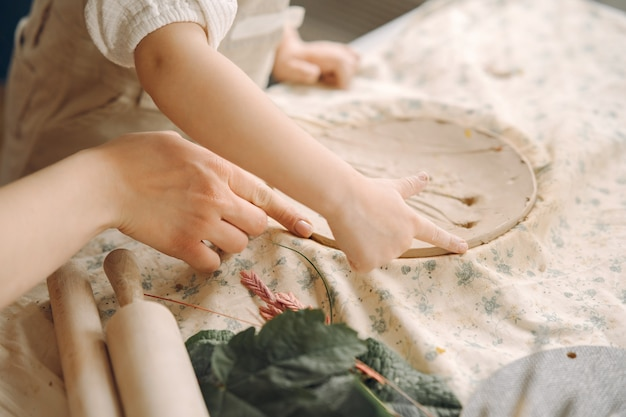 Het meisje maakt een kleiplaat en versiert het