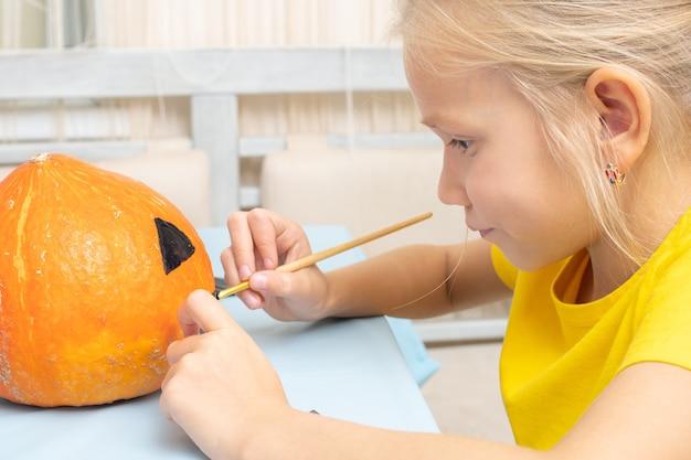 Het meisje maakt een lantaarn van een pompoen, zittend aan de tafel in de keuken thuis. achtergrond voor halloween-feest en familielevensstijl