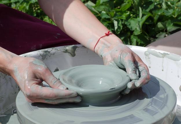 Het meisje maakt een pot klei op de piep van een pottenbakker