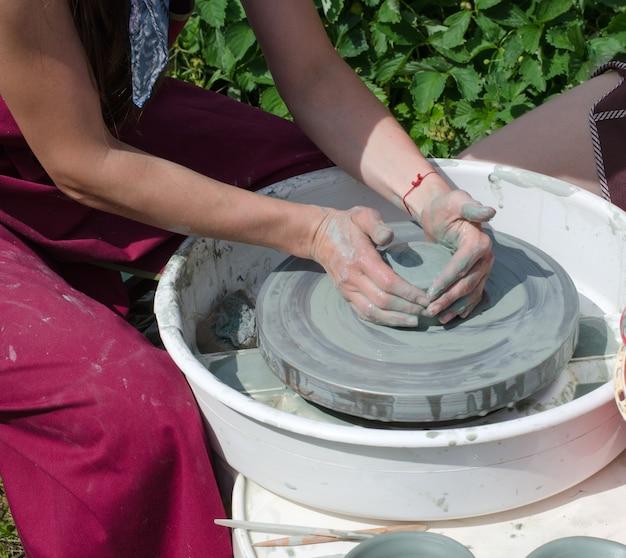 Het meisje maakt een pot klei op een pottenbakkerswiel.