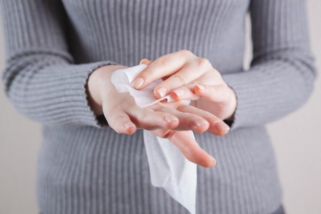 Het meisje maakt haar handen schoon met een nat servet