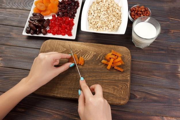 Het meisje maakt haar ontbijt klaar. snijden van gedroogde vruchten in havermoutpap op een snijplank. handig en gezond ontbijt. donkere houten tafel, bovenaanzicht