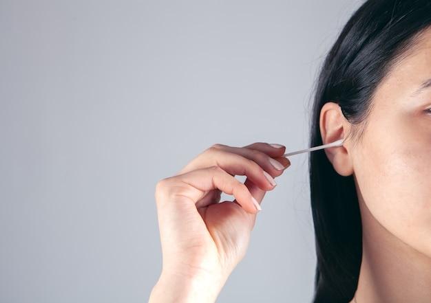 Het meisje maakt haar oren schoon met een stok