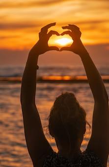 Het meisje maakt harthanden bij zonsondergang