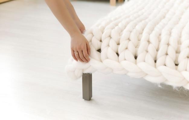 Het meisje maakt het bed op met een deken