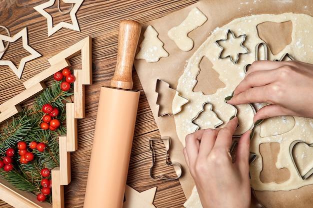 Het meisje maakt peperkoek kerstkoekjes met behulp van formulier om te koken
