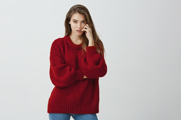 Het meisje maakt zich zorgen terwijl het wachten op resultaten van test. portret van knappe vrouwelijke vrouw in rode losse trui bijten nagels terwijl op zoek met doordachte en serieuze expressie