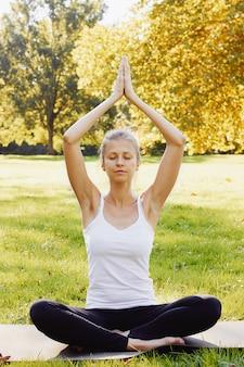 Het meisje mediteert terwijl in openlucht het beoefenen van yoga in park