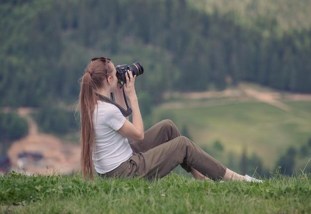 Het meisje met camera zit op een heuvel en fotografieaard. zomerdag