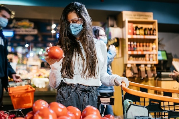 Het meisje met chirurgisch masker gaat tomaten kopen.