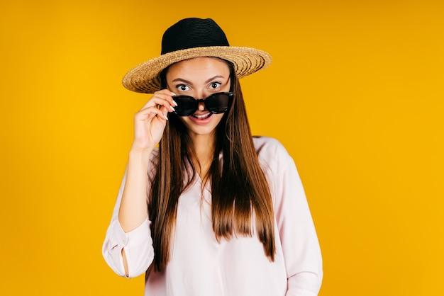 Het meisje met de hoed, verrast, zette haar bril met haar hand op haar neus en kijkt ernaar. studio geel