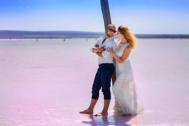 Het meisje met de jongen poseert buiten bij het zoute meer tegen de achtergrond van de berg