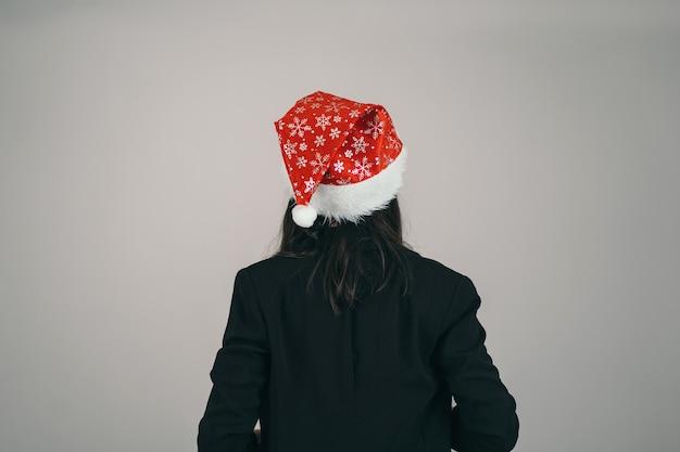 Het meisje met de kerstmuts. een man doet een wens voor kerstmis. de kerstman staat met zijn rug.