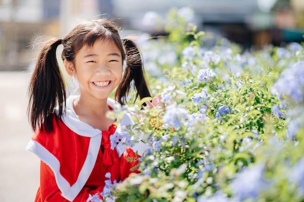 Het meisje met de sandy-outfit glimlacht en lacht vrolijk. tussen de bloemen