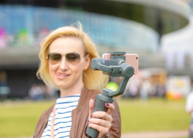 Het meisje met de telefoon op de stabilisator leidt de videoblog. ze neemt zichzelf mee naar de camera smartphone