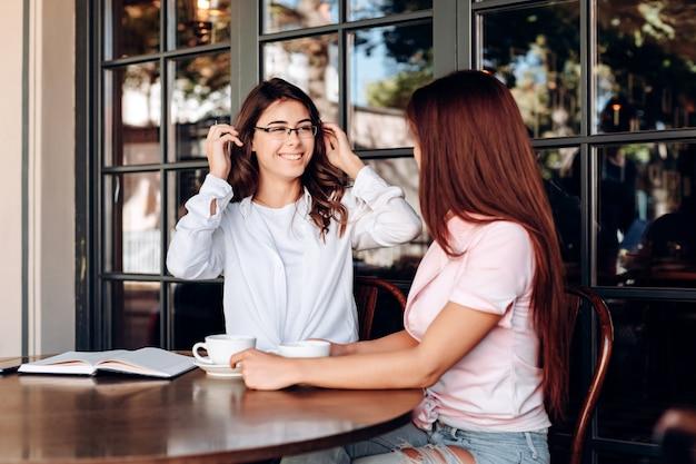 Het meisje met een bril glimlacht oprecht naar zijn gesprekspartner