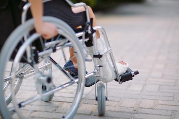 Het meisje met een gebroken been zit in een rolstoel