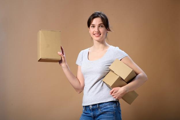 Het meisje met een gelukkige glimlach draagt en toont een doos. reclame concept