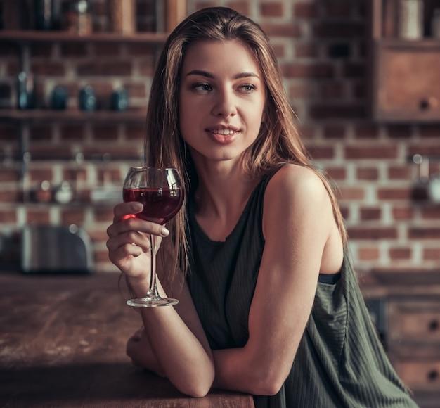 Het meisje met een glas rode wijn kijkt weg.