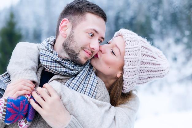 Het meisje met een hoed kust haar vriendje op zijn wang en knuffelt hem vanaf de achterkant in de winter