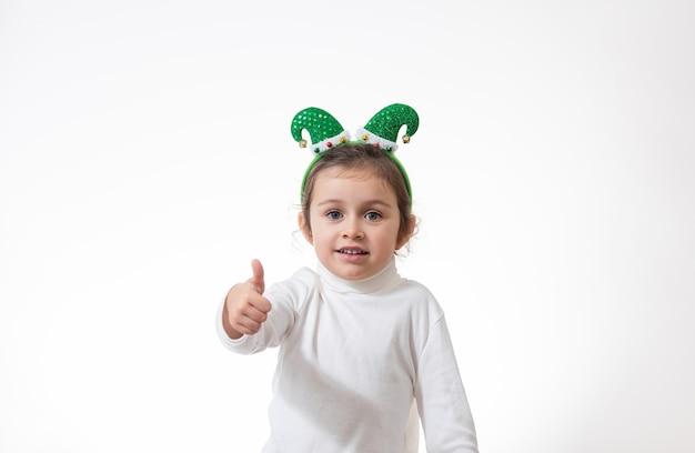Het meisje met een hoepel in de vorm van een elfhoed op haar hoofd laat een vinger zien.