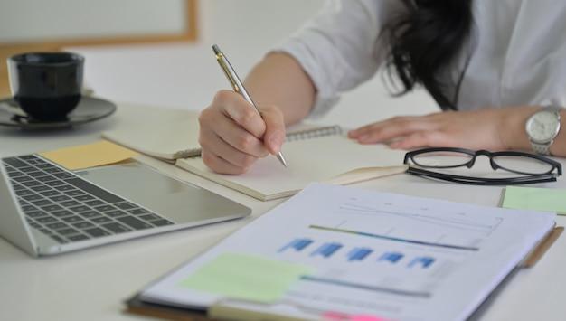 Het meisje met een in hand pen registreert de bedrijfprestaties met grafiek en laptop op het bureau.