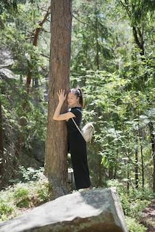 Het meisje met een rugzak koestert een boom met haar gesloten ogen in het bos. zonnige zomerdag.