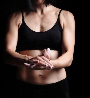 Het meisje met een sportencijfer kleedde zich in zwarte hoogste klappen in haar handen met wit magnesiumoxide