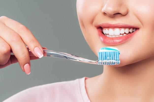 Het meisje met gezonde witte tanden houdt een tandenborstel en glimlacht. mondhygiëne concept