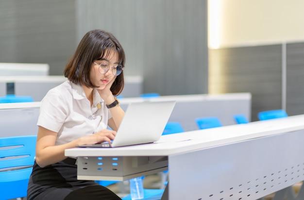 Het meisje met glazen bekijkt laptop terwijl het doen van thuiswerk