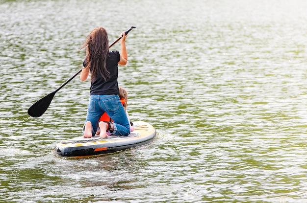 Het meisje met haar baby stand up paddle boarding (sup)