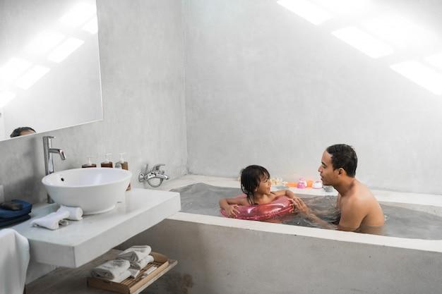 Het meisje met haar vader neemt samen een bad