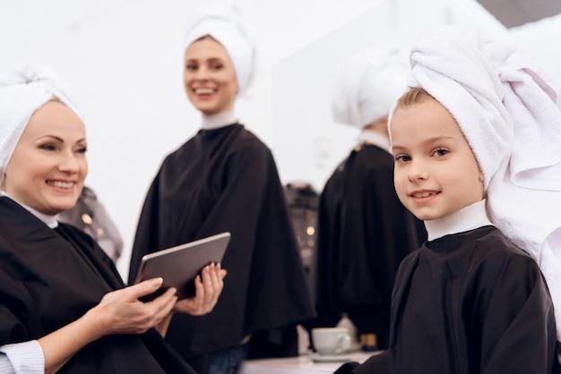 Het meisje met handdoek op hoofd is met haar familie in schoonheidssalon.